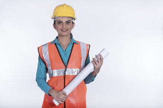 Portrait of architect student woman with blueprints - protective helmet and reflective jacket. White background