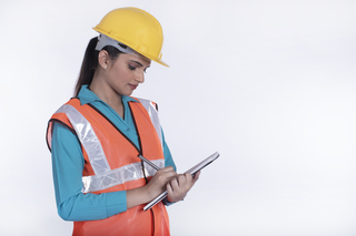 Image of a female architect working on construction site and writing with a pen in her  notebook - White background