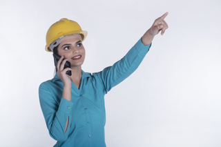 Smiling female architect is pointing at a building while talking on a mobile phone - White background
