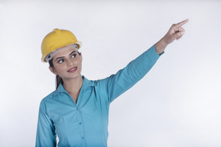Portrait of a female architect pointing at building with a finger - Business concept
