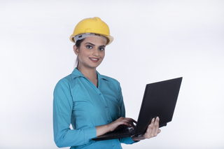 Portrait of a smiling architect woman working on laptop - white background with copy space