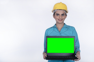 Smart Indian architect woman holding a laptop with a white background - Wearing a hard hat for safety