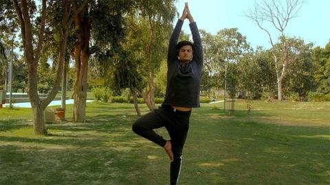 Zoom out shot of young Indian man doing Vrikshasana/tree pose Yoga Asana