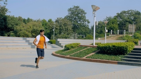 Muscular young man jogging in a green park - a healthy lifestyle concept