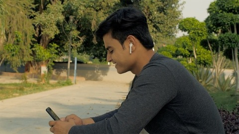 Indian youngster browsing mobile while sitting near green trees - relaxation concept