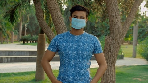Portrait of a charming young Indian boy wearing a medical mask in a public park