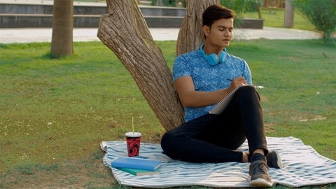 Attractive boy writing in a notebook while leaning against a tree in the park