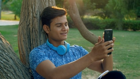 Attractive Indian youngster talking on a video call while studying in a park