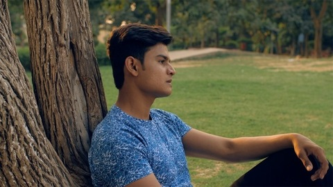Upset young man thinking about his life while sitting near a tree trunk in the park