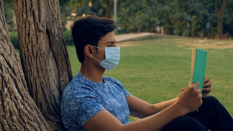 Young man wearing a medical mask reading a book while sitting in a park - COVID / Coronavirus pandemic