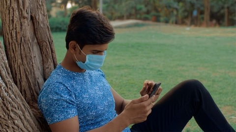 Indian youngster wearing a medical mask browsing his smartphone in the park - COIVD / Coronavirus pandemic