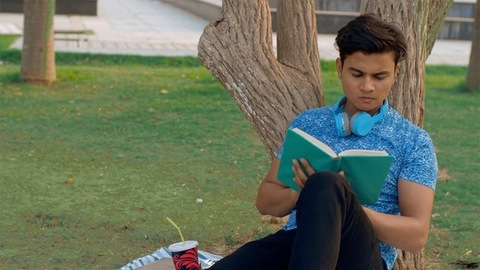 A young man eating snacks while studying under a tree in a beautiful park