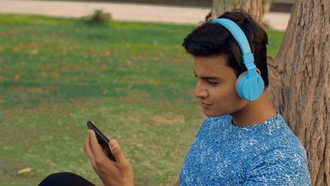 A smiling youngster with a blue headphone checking his mobile in the park