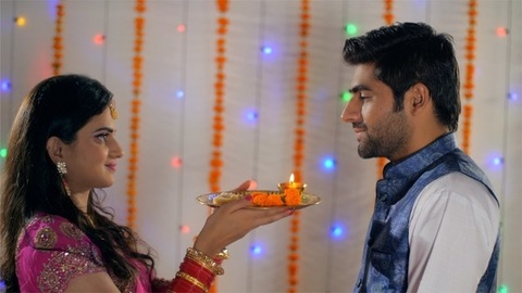 Happy newly-wed couple performing Karwa Chauth rituals in traditional wear