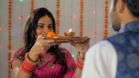 Indian husband-wife happily celebrating the Karwa Chauth festival together