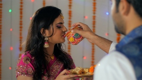 Newly-wed Indian couple happily performing Karwa Chauth rituals together