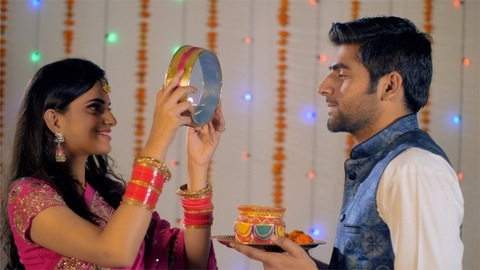 Newly-wed Indian couple celebrating Karwa Chauth festival in traditional wear
