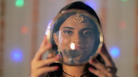 Closeup shot - Married Indian woman happily performing Karwa Chauth rituals