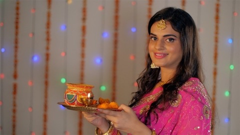 A beautiful married woman happily posing while holding a festival Puja thali