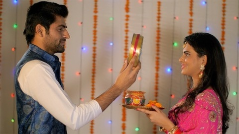 A newly-wed couple celebrating Karwa Chauth festival together in traditional wear
