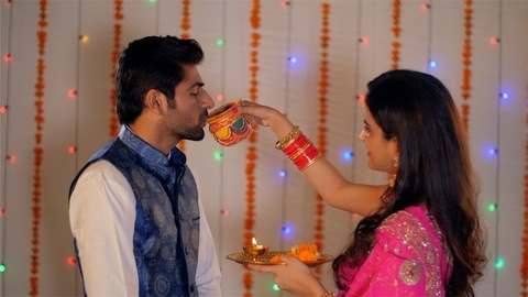 Young modern couple performing Karwa Chauth rituals in traditional clothing