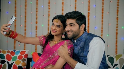 Indian couple happily posing while capturing selfies during the festive season
