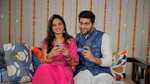 Attractive Indian couple doing online shopping for Diwali presents using a smartphone