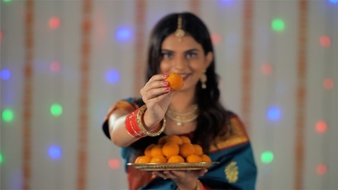 Beautiful Indian woman offering delicious sweets while looking at the camera