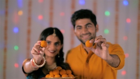 A beautiful newly married Indian couple celebrating Diwali and offering besan ladoo
