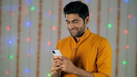 Attractive man in traditional Indian wear smiling and texting on a smartphone - Festive decor