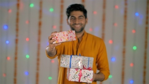 A Young Indian man in ethnic attire offering a wrapped Diwali gift