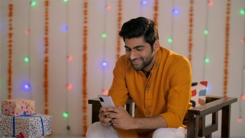 Young Indian man chatting on phone wearing traditional kurta - festival concept