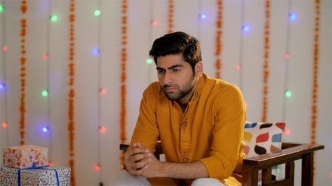 Frustrated Indian man sitting alone on the sofa on the occasion of Diwali