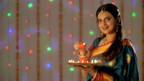 Good looking Indian female in saree holding an oil lamp celebrating her first Diwali