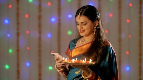 Newly married Indian woman checking her phone holding a plate of oil lamps - Diwali decoration
