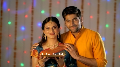 A newly married couple celebrating Diwali with brightly lighted Diyas