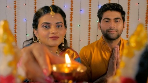 Attractive Indian woman offering brightly lit Diya to Lord Ganesha and Laxmi