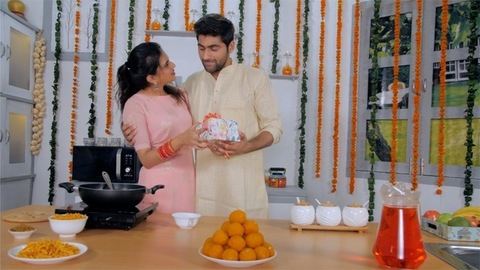 A loving husband brings a Diwali gift for his pretty wife in the kitchen