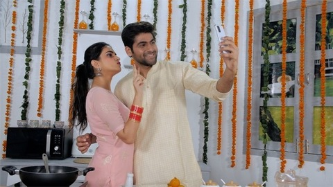 Indian husband clicking a selfie on mobile while his wife is busy in the kitchen