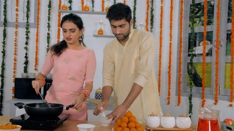 Newlywed young husband-wife cooking together in a decorated kitchen