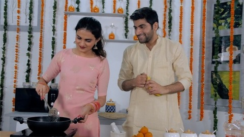 Indian wife cooking in the kitchen while her husband chatting and eating fruits