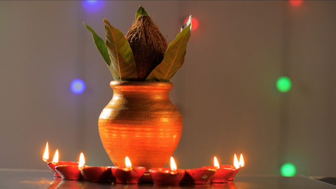 Hindu puja Kalash with coconut and mango leaves circled with earthen Diyas