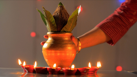 Female's beautiful hand keeping a copper puja Kalash in between some oil lamps