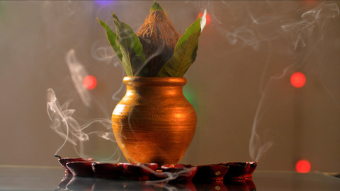 Copper Kalash with coconut and mango leaves in a peaceful puja room