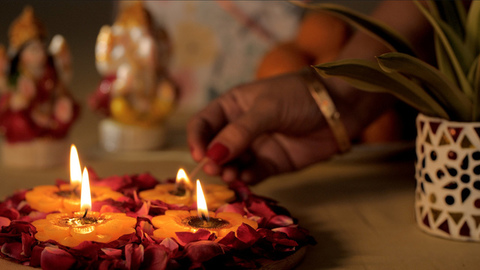Female's hand lighting a Diya with Hindu God idols and laddus in the background