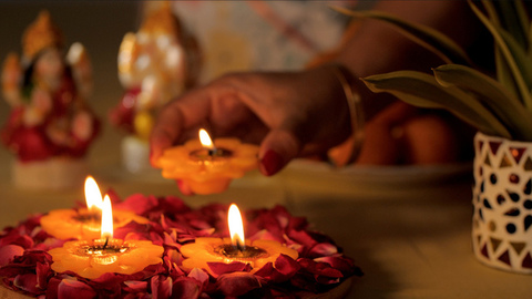 Woman's hand keeping beautiful wax Diya with other Diyas on flower petals