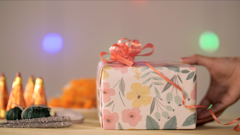 Woman's hand keeping a colorful gift box with firecrackers and flower petals