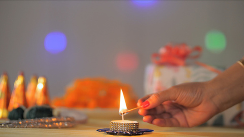 Female's beautiful hand lightening a small wax Diya with Diwali props in the background