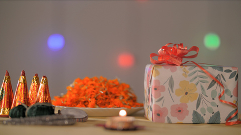 Beautiful Diwali festive space with gifts, firecrackers, wax lamp, and flower petals