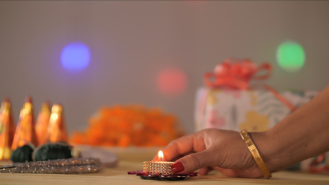 Indian woman's hand keeping a small wax Diya on a table full of Diwali props